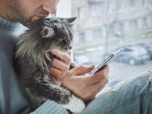 Den unga mannen sitter på fönsterbrädan, rymmer en härlig fluffig kattunge på hans varv royaltyfri fotografi
