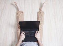 Den unga mannen sitter på golvet med den svarta bärbara datorn royaltyfri fotografi