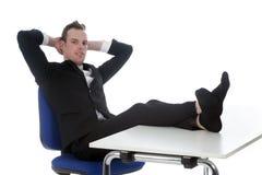 Den unga mannen sitter på kontorsstol med hans fot på tabellen Arkivbilder