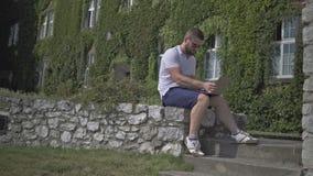 Den unga mannen sitter på väggen och startar att skriva på bärbara datorn arkivfilmer