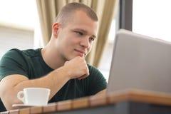 Den unga mannen sitter, ser bärbara datorn och surfar internet Royaltyfri Fotografi