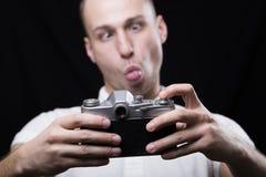Den unga mannen skelade hans ögon och visningtunga, att fotografera som var högt arkivfoton