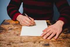 Den unga mannen skrivar ett brev Royaltyfri Fotografi
