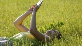 Den unga mannen skriver något på hans smartphone, medan ligga på naturen på grönt gräs i sommar lager videofilmer