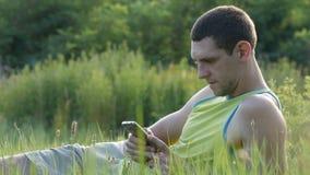 Den unga mannen skriver något på hans smartphone, medan sitta på naturen på grönt gräs i sommar arkivfilmer