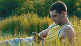 Den unga mannen skriver något på hans smartphone, medan sitta på naturen på grönt gräs i sommar lager videofilmer