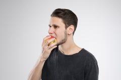 Den unga mannen som äter äpplet i svart skjorta, isolerade studion Royaltyfria Bilder