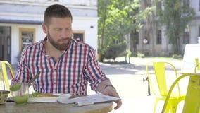 Den unga mannen som äter lunch och den läs- tidningen, glidare sköt vänstert arkivfilmer