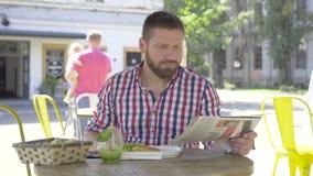 Den unga mannen som äter lunch och den läs- tidningen, glidaren och pannan, sköt vänstert arkivfilmer
