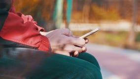 Den unga mannen som använder en mobiltelefon på en bänk i staden, parkerar stock video
