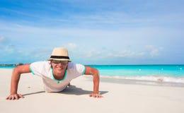 Den unga mannen som att göra skjuter, ups på den sandiga stranden Fotografering för Bildbyråer