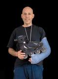 Den unga mannen som bär en arm, gjuter efter en åka skridskor olycka Arkivfoto