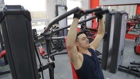Den unga mannen som böjer bröstkorgen, tränga sig in på idrottshallmaskinen arkivfilmer