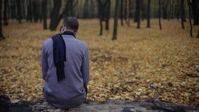 Den unga mannen som bara sitter i höst, parkerar, känner fördjupningen, nostalgi, ensamhet arkivbild