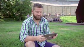 Den unga mannen som bläddrar minnestavlan, ler för kamera steadicam arkivfilmer