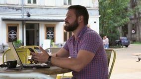 Den unga mannen som bläddrar smartphonen i kafét, glidare sköt rätt stock video