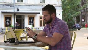 Den unga mannen som bläddrar smartphonen i kafét, glidare sköt vänstert stock video