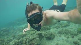 Den unga mannen som blåser snorkla maskeringen för, kvitterar tryck i öron, medan dyka i havet Video stund för manskytteselfie stock video