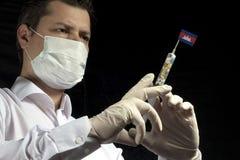Den unga mannen som en doktor ger en medicinsk injektion till den kambodjanska flaggan Arkivbild