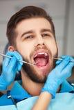 Den unga mannen som får hans tänder, kontrollerade vid en tandläkare Royaltyfri Bild