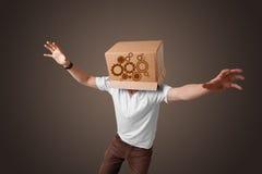 Den unga mannen som gör en gest med en kartong på hans huvud med, sporrar w Fotografering för Bildbyråer