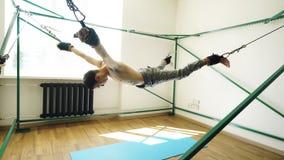 Den unga mannen som gör exircise på att inkvartera yogautrustning och, drar hans armar och ben med rep Fotografering för Bildbyråer