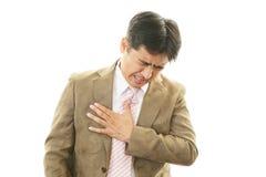 Den unga mannen som har bröstkorgen, smärtar Arkivfoto