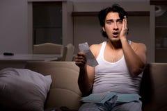 Den unga mannen som hemma ber?knar expencesnatt royaltyfri bild