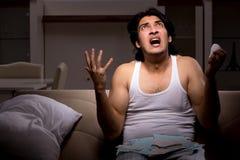 Den unga mannen som hemma ber?knar expencesnatt arkivfoto