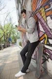 Den unga mannen som igen lutar en vägg som täckas i grafitti och smsar på hans telefon, skateboard är bredvid honom Arkivbild