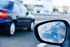 Den unga mannen som kör en bil, reflekterade i vingspegeln Royaltyfri Foto