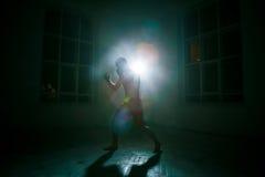 Den unga mannen som kickboxing på svart bakgrund royaltyfria bilder
