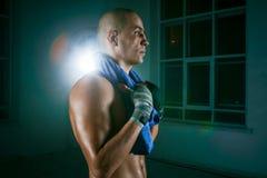 Den unga mannen som kickboxing på svart bakgrund arkivfoto