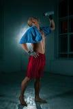 Den unga mannen som kickboxing på svart bakgrund arkivbild