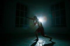 Den unga mannen som kickboxing på svart bakgrund royaltyfri fotografi