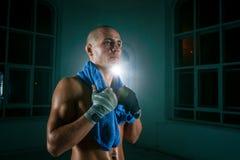 Den unga mannen som kickboxing på svart bakgrund arkivfoton