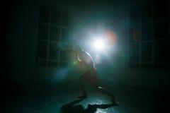 Den unga mannen som kickboxing på svart bakgrund royaltyfri bild
