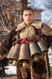 Den unga mannen som kläs som Kuker, hoppar med mässingsklockor Royaltyfri Fotografi