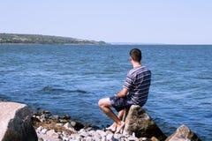 Den unga mannen som kopplar av på stranden Arkivbilder