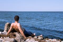Den unga mannen som kopplar av på stranden Royaltyfri Bild