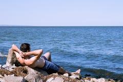 Den unga mannen som kopplar av på stranden Arkivbild