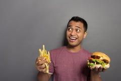 Den unga mannen som ler och, ordnar till för att äta en hamburgare Arkivbild