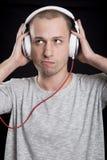 Den unga mannen som lyssnar till musik i hörlurar med ett vresigt, uttrycker Arkivbilder