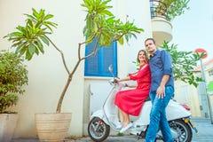 Den unga mannen som omfamnar flickvänsammanträde på den parkerade sparkcykeln på den medelhavs- stadsgatan med exotisk treesin, l royaltyfri fotografi
