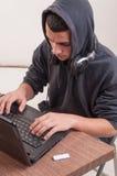 Den unga mannen som placeras på hans skrivbord som arbetar med bärbara datorn och, lyssnar mu Arkivbilder