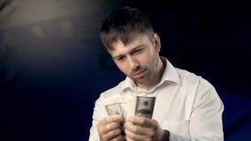 Den unga mannen som räknar några pengar stirrar på kameran och når uppmärksamt därefter, ut bestämd mängd pengar arkivfilmer