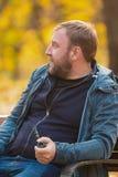 Den unga mannen som röker tobakröret parkerar in Royaltyfri Foto