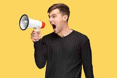 Den unga mannen som rymmer en megafon Royaltyfri Fotografi