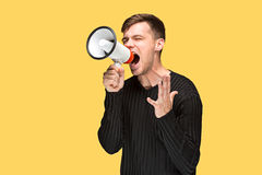 Den unga mannen som rymmer en megafon Royaltyfri Foto