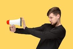 Den unga mannen som rymmer en megafon Royaltyfria Bilder